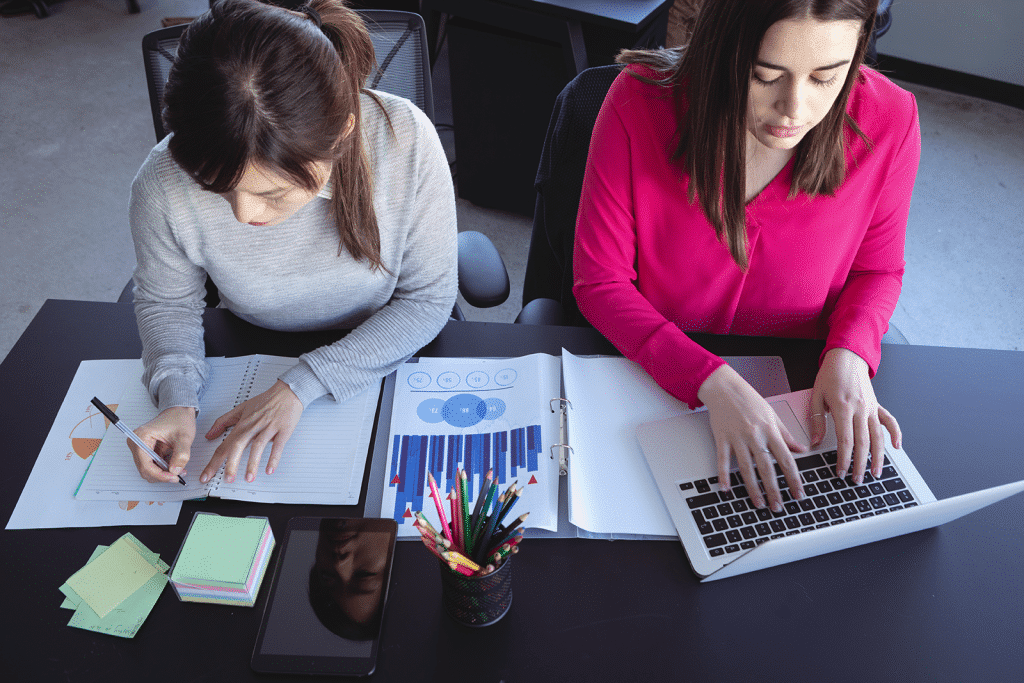 two woman working together at a desk