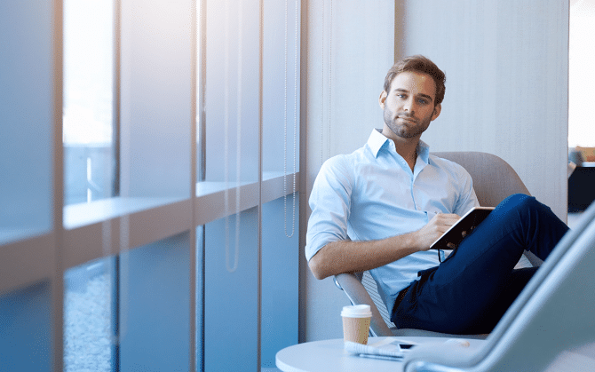 Smartly dressed man, sitting writing on a notepad